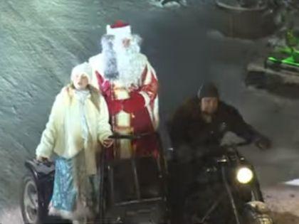 """Лидер """"Ночных волков"""" за рулем мотоцикла, на котором едут Снегурочка и Дед Мороз"""