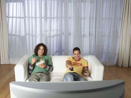 Молодые люди едят перед телевизором